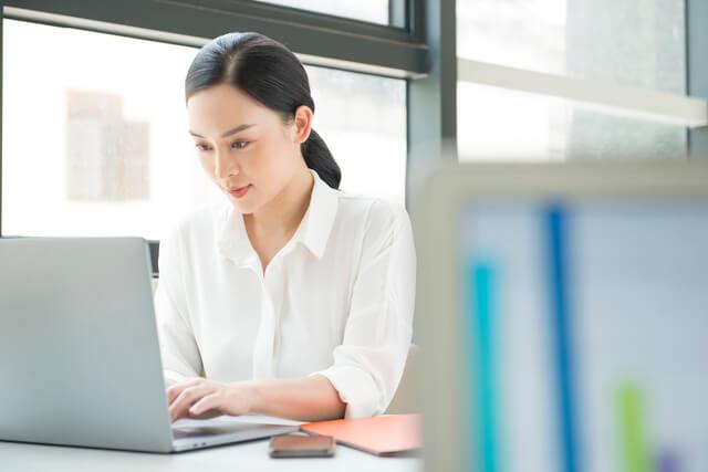 パソコンを操作して社員インタビュー記事の執筆を行う女性