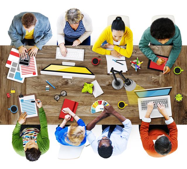 グループが1つの机に向かって仕事をしている様子
