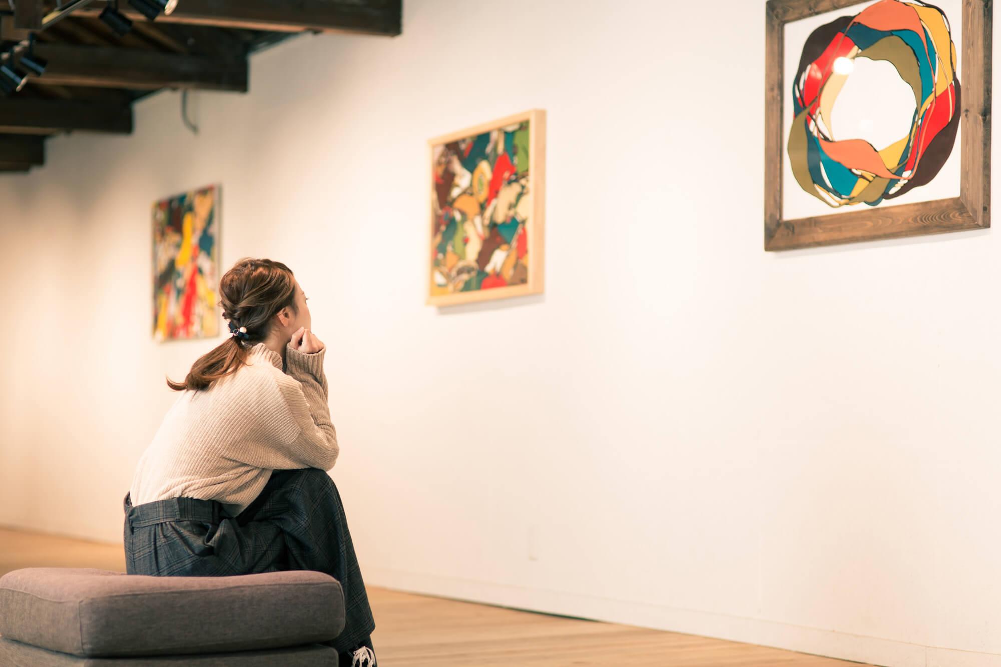 個展や展覧会を鑑賞しているお客。近い将来を見据えているイメージ